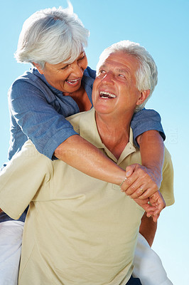 Buy stock photo Playful senior couple enjoying piggyback ride against sky