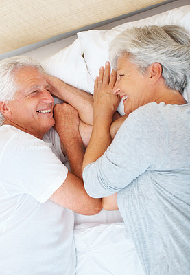 Buy stock photo Senior couple on bed smiling and looking at each other