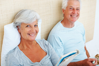 Buy stock photo Portrait of senior couple sitting on bed with woman reading book and man eating breakfast