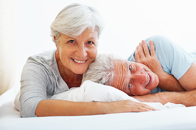 Buy stock photo Closeup portrait of senior couple lying in bed and giving you an attractive smile