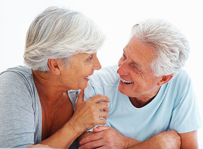 Buy stock photo Closeup of senior couple smiling and looking at each other while relaxing
