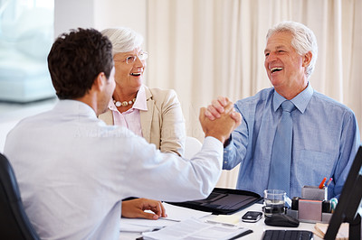 Buy stock photo Portrait of a happy mature couple holding hand of a financial advisor at office