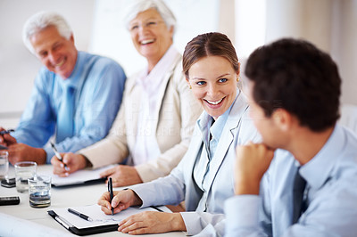 Buy stock photo Portrait of a beautiful young businesswoman smiling while sitting in a meeting with colleagues