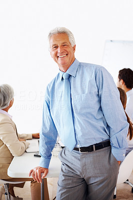 Buy stock photo Portrait of a successful old businessman standing relax with colleagues in background