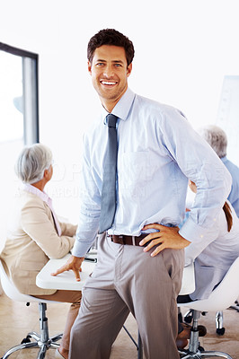 Buy stock photo Portrait of a relaxed businessman standing in front of his team in a presentation at office