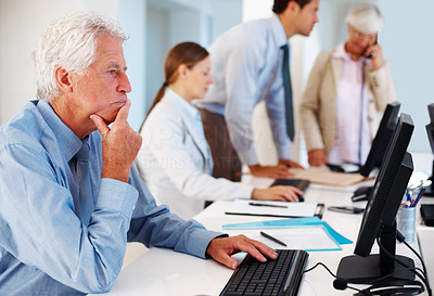 Buy stock photo Portrait of a mature businessman thinking while working on a computer at work
