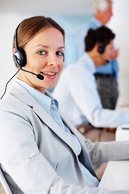 Buy stock photo Pretty customer care executive at her desk with colleagues at the back