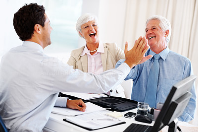 Buy stock photo Happy old couple giving high five to a investment advisor during a meeting at office