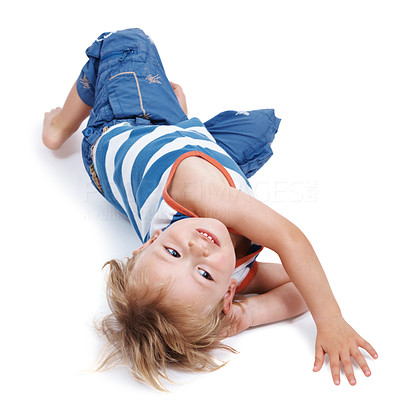 Buy stock photo Portrait of a cute little boy lying on floor looking in playful mood against white background
