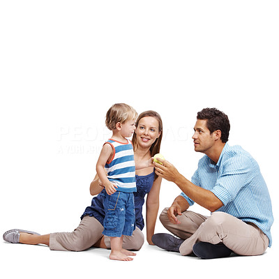 Buy stock photo Happy young couple sitting on floor with their small kid and playing over white background - Copyspace