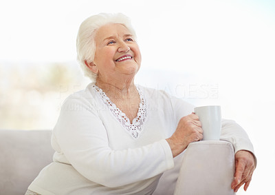 Buy stock photo Portrait of a happy senior woman relaxing on sofa while holding a cup of tea or coffee