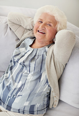 Buy stock photo Portrait of a senior woman relaxing on a sofa with her hands behind her head