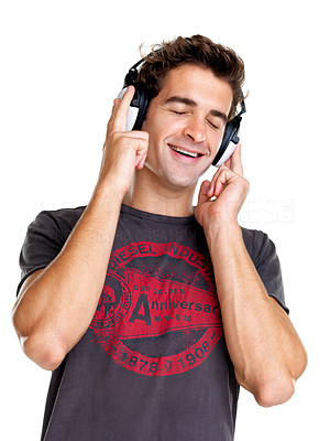 Buy stock photo Portrait of a handsome young man listening to music on headphone against white background