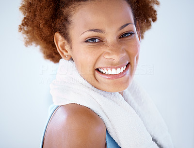 Buy stock photo Closeup portrait of a smiling young woman relaxing after her exercise against grey background