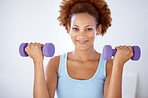 Happy young girl lifting dumbbells