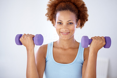 Buy stock photo Portrait of a smiling woman doing lifting exercise with dumbells in hands