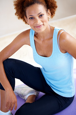 Buy stock photo Portrait of a happy and relaxed young woman sitting on yoga mat at gym