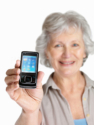 Buy stock photo Portrait of a happy senior female showing her cell phone isolated against white