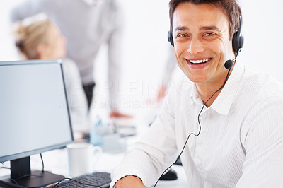 Buy stock photo Smiling business man at work using headset and computer with colleagues in background