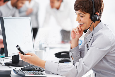 Buy stock photo Female customer service reading text message with colleagues in background
