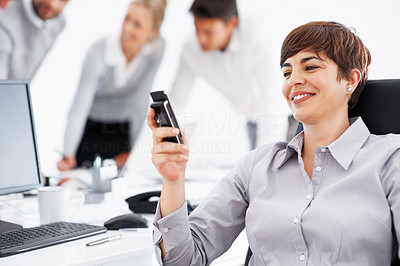 Buy stock photo Beautiful business woman reading text message on cell phone with team discussing in background