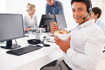 Buy stock photo Happy business man eating at desk with colleagues in background