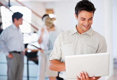 Buy stock photo Handsome business man working on laptop and smiling with executives in background