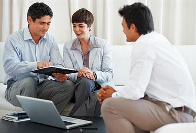 Buy stock photo Happy couple taking financial advice from consultant