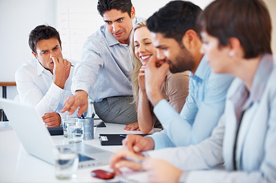 Buy stock photo Business colleagues discussing project during meeting with man pointing at laptop