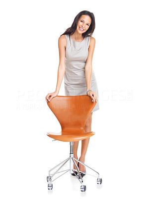 Buy stock photo Confident young woman standing with a chair isolated on white background