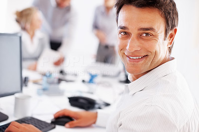 Buy stock photo Closeup of smiling male executive using computer with colleagues discussing in background