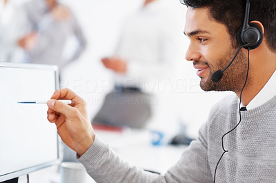 Buy stock photo Business man using headset and pointing at computer with colleagues in background