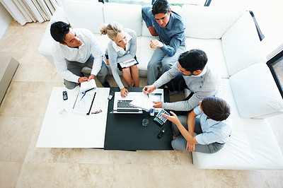 Buy stock photo High angle view of male executive explaining project with his colleagues in meeting