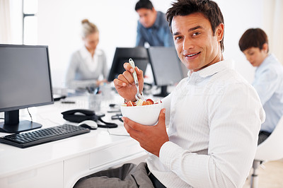Buy stock photo Male executive eating fruit salad in front of computer with colleagues in background