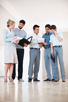 Buy stock photo Full length of business colleagues reviewing business plan in the corridor