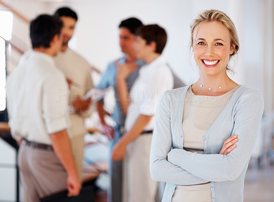 Buy stock photo Smiling business woman with arms crossed and colleagues discussing in background
