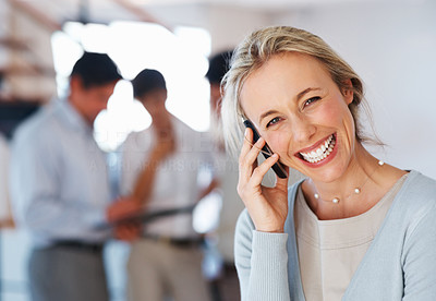 Buy stock photo Closeup of cheerful business woman talking on cellphone with colleagues in background