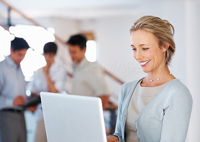 Buy stock photo Beautiful female executive using laptop and smiling with colleagues in background