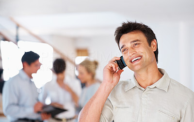 Buy stock photo Smart smiling business man having conversation on cellphone and looking away with colleagues in background