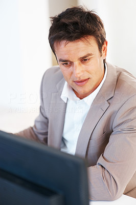 Buy stock photo Handsome business man working on computer and looking at the screen