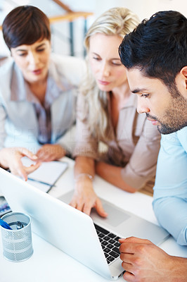 Buy stock photo Business team sitting at table using laptop