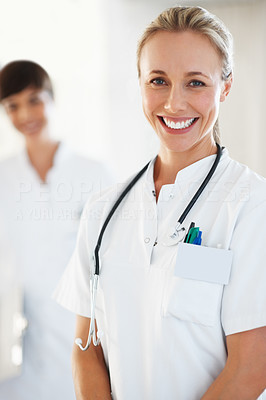 Buy stock photo Portrait of attractive medical doctor smiling with colleague in background