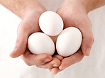 Human hand holding white eggs
