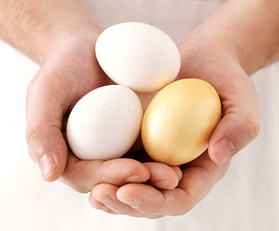 Buy stock photo Closeup of one golden egg among usual eggs in human hand