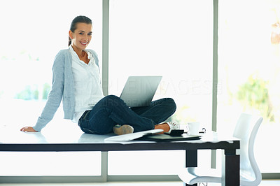 Buy stock photo Happy woman sitting on table with laptop in lap