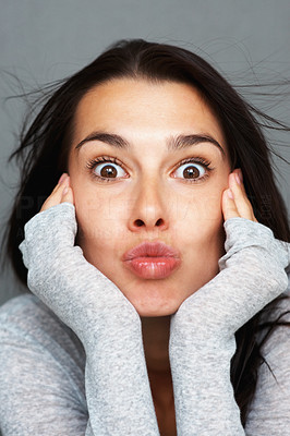 Buy stock photo Woman playfully puckering her lips while giving a surprised look