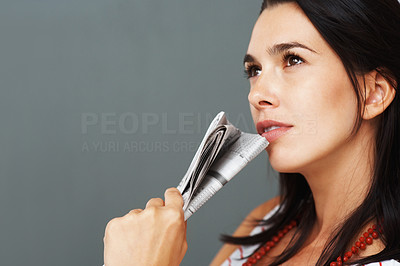 Buy stock photo Pretty woman holding up newspaper while deep in thought