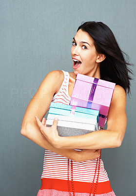 Buy stock photo Pretty woman carrying a stack of gifts in his arms, isolated on a grey background