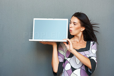 Buy stock photo Woman looking surprised while holding up laptop computer