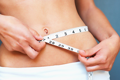 Buy stock photo Cropped image of woman measuring her waist